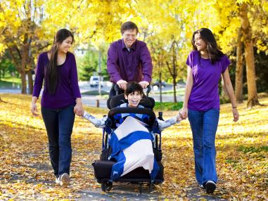 Smiling family walking outside in the fall, Dad pushing his Son who is in a wheelchair and Mom and daughter holding son's hands