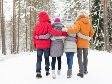 Family of four walking away from camera, arm in arm outside during winter