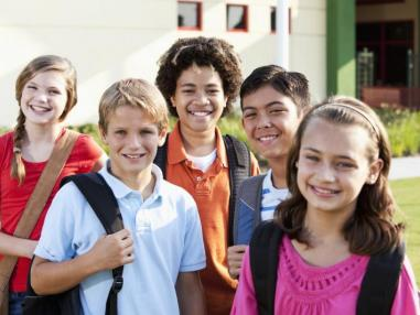 Diverse group of school aged children going to school smiling with their backpacks