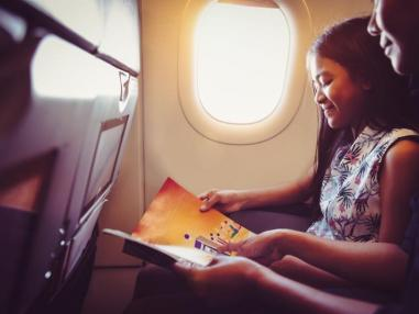 parent and child seated on airplane and smiling while reading a book